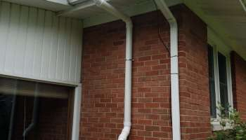 radon mitigation system along brick wall outside