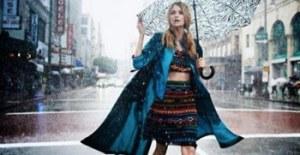 雨の日にレインコートを着る女性