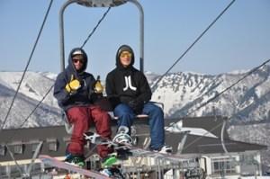 外国人がスノボウェアを着てリフトに乗る