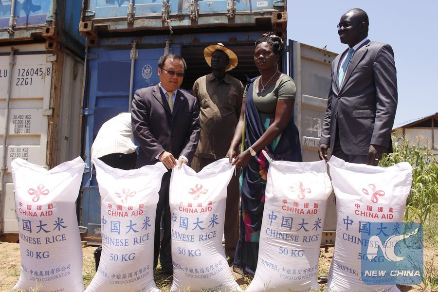 Hang Yi (L), Economic and Commercial Counselor at the Chinese Embassy in South Sudan, hands over some of the emergency food aid to Martha Nyamal (2nd R). This food ended up in the hands of government officials who distributed it among themselves(Photo: file)