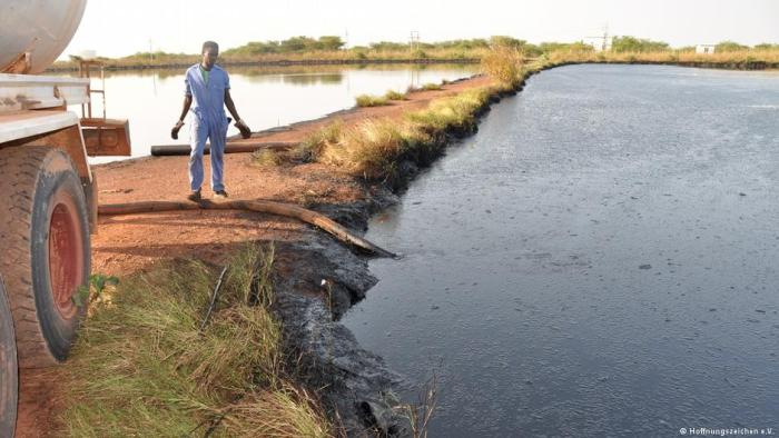 A young South Sudanese oil worker releasing oil waste into a nearby water sources. Areas around oil fields in South Sudan face serious environmental damage and related diseases(Photo: supplied)