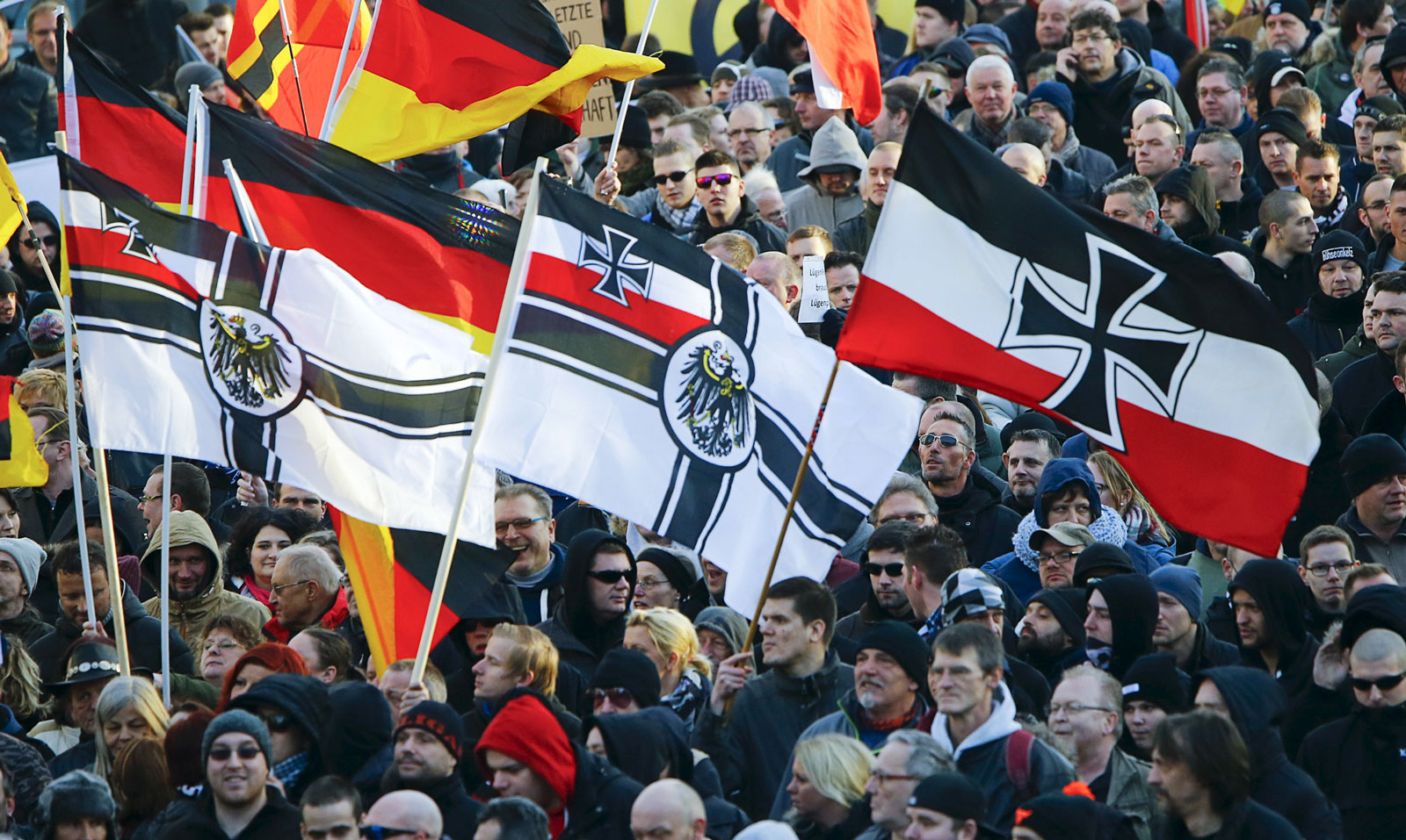 Supporters of the anti-immigration right-wing movement Pegida (Patriotic Europeans Against the Islamisation of the West) carry versions of the Imperial War Flag (Reichskriegsflagge) during a demonstration march, in reaction to mass assaults on women on New Year's Eve in Cologne, Germany, January 9, 2016