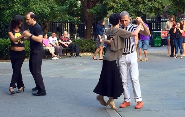 Couples dance in a park