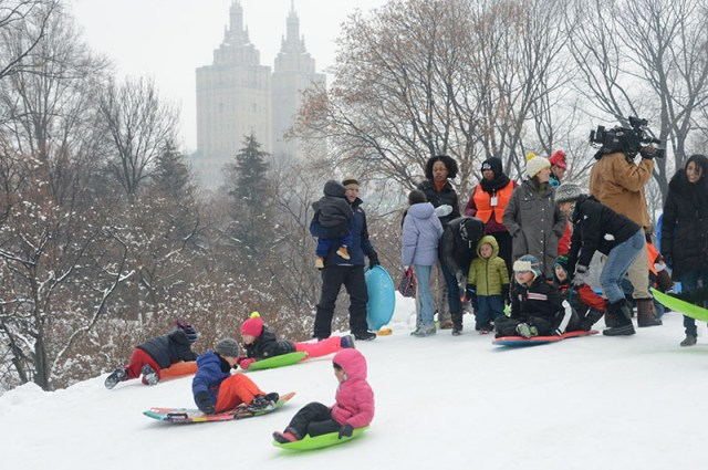 Parents look on as kids sled down a hill covered in snow.