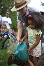 Ranger instructing child about plant watering