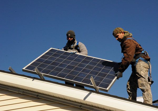 Two men installing a solar panel on a roof.
