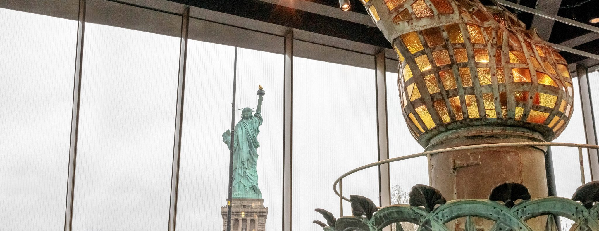 The Statue of Liberty in the distance and a close-up of the original torch in an accessible museum.