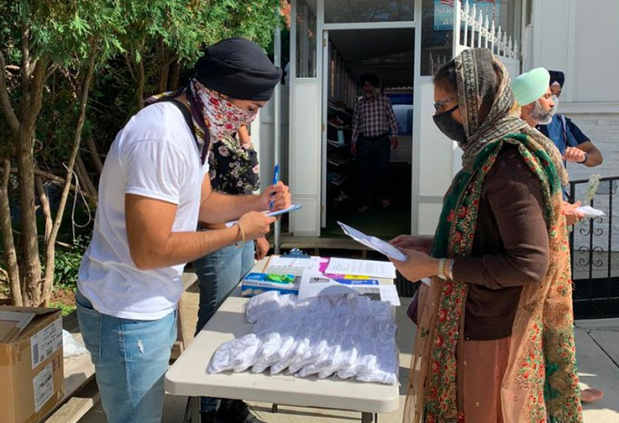An India Home community ambassador distributes masks at a local Sikh house of worship.