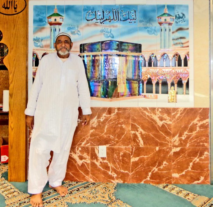 Abdul Aziz from Pakistan in front of painting of Mecca at Masjid Noor-Ul-Huda, Bronx, New York. Photo: Melissa Kimiadi/A Journey through NYC religions