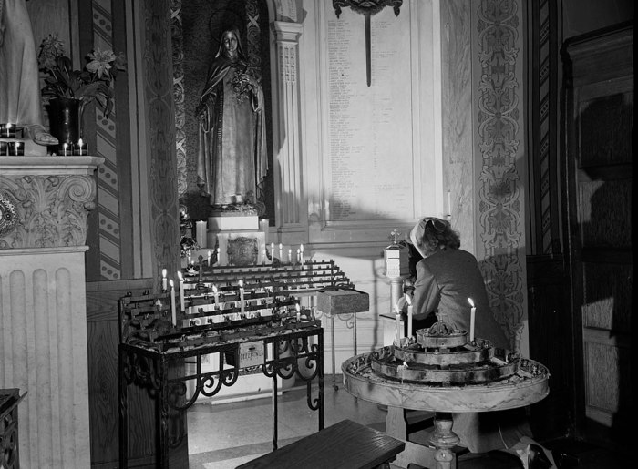 Lighting a candle & prayer on D-Day, 12 Noon, June 6, 1944 at Saint Vincent de Paul's Church, Manhattan, NY. Photo: Unknown/OWI Collection Library of Congress.
