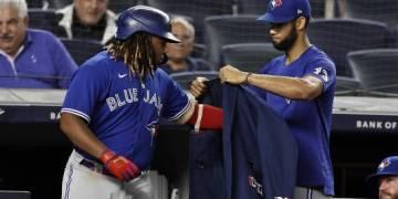 El cubano Lourdes Gurriel, de los Azulejos de Toronto, coloca la chaqueta de los jonrones al dominicano Vladimir Guerrero Jr., el miércoles 8 de septiembre de 2021, en un juego ante los Yanquis de Nueva York (AP/Adam Hunger)
