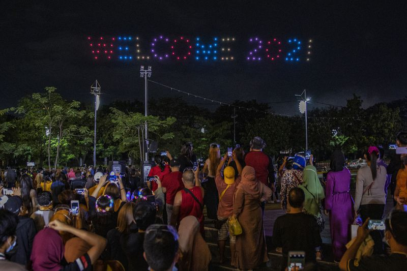 People in Manila, Philippines, watch a drone show during New Year's Eve celebrations at a park. (Photo by Ezra Acayan/Getty Images)