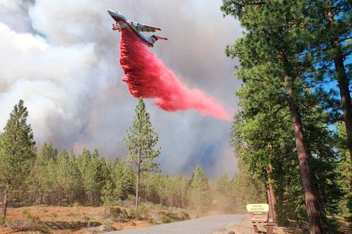 In this photo provided by the Bootleg Fire Incident Command, a tanker drops retardant over the Mitchell Monument area at the Bootleg Fire in southern Oregon on Saturday, July 17, 2021. The 569-square-mile Bootleg Fire is burning 300 miles southeast of Portland in and around the Fremont-Winema National Forest, a vast expanse of old-growth forest, lakes and wildlife refuges.