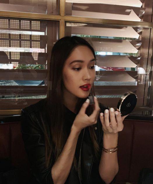 Aimee Cheng-Bradshaw trying on Clé de Peau's Radiant Liquid Rouge Shine at Idlewild