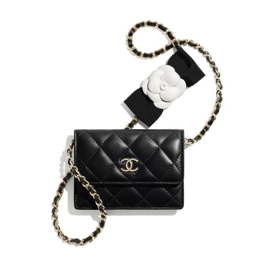 Black clutch in leather embellished with a bow and a camellia
