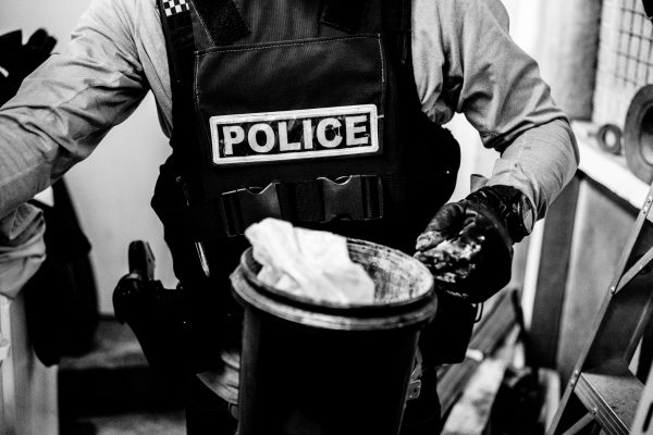 Accompanied by members of an armed offenders squad, police officers raid a small private warehouse in a Wellington industrial estate suspected of being involved in the distribution of methamphetamine. Articles are tested for residues on site, gathered and documented for subsequent prosecution.