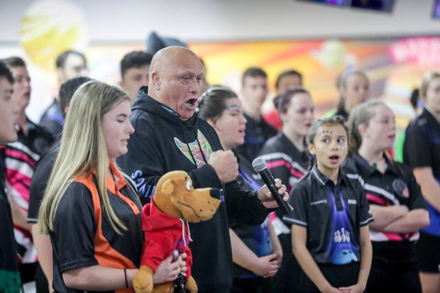 Henare O'Keefe, a member of the Hastings District Council, sings the national anthem with competitors at the NZ Junior Youth Tenpin Bowling national championships, Hastings. Photo / Warren Buckland