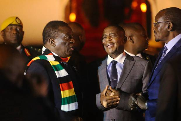Zimbabwean President Emmerson Mnangagwa, left, arrives in Harare after cutting short his fund-raising trip in order to address the country's economic crisis and crackdown. Photo / AP