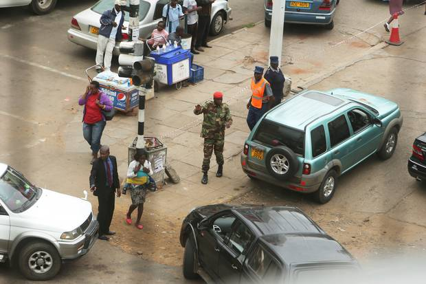 A soldier controls a fuel queue in Harare on January 22. Photo / AP