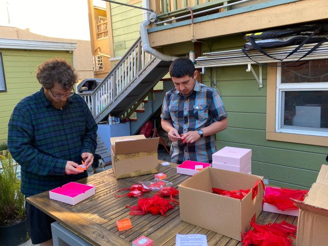 Oakland Uptown Rotary members Will Klyver and Armando Cortes unboxing earrings and bagging into organza bags.