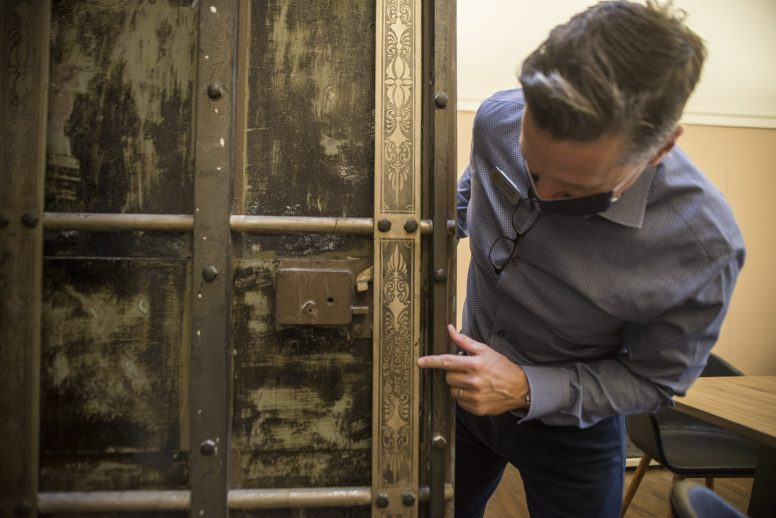 J. Trent Stoner shows off the detail of a vault door where fur coats were once stored at the Boulevard Arcade building on South Boulevard. The inscrpition reads 'Diebold Safe & Lock Co Canton, O.'| ALEX ROGALS/Staff Photographer