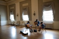 A small group learns guitar in the 19th Century ballroom.