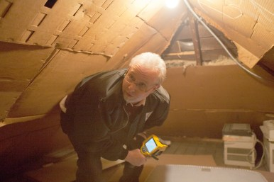 House Detectives: Michael Ruehle, a BPI energy analyst, in an attic crawl space of the Lewis home in Oak Park. Ruehle uses thermal imaging technology to determine air leaks.
