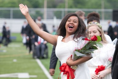 A happy graduate waves like a pageant queen as she walked by the stands and spotted family and friends during a commencement ceremony at Oak Park and River Forest High School. In all, 829 seniors graduated.