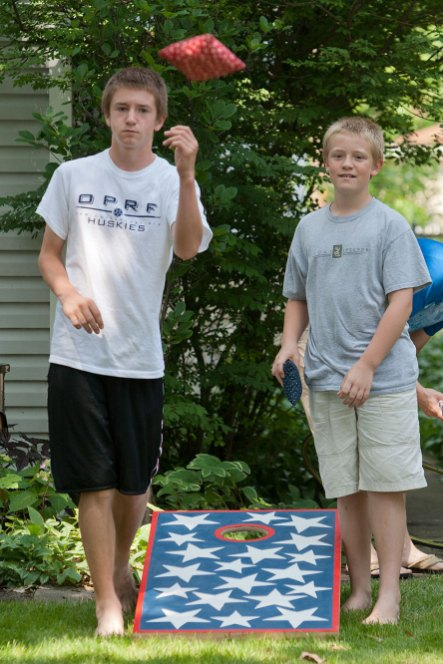 Jeremiah Kennedy, left, and his brother, Anderson Kennedy, play baggo after the parade passed them by.