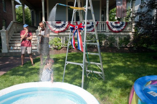 little girl reaches out to water flowing from a shower head set up at the home of Al Schwartz for his guests to keep cool during the parade. In years past, when the parade fell on a particularly hot day, Schwartz has set up the shower in the street for parade participants.