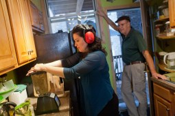 Steyer dons ear protection as she grinds fruits and vegetables into a breakfast juice for her and husband, Paul Geiger. (David Pierini/staff photographer)