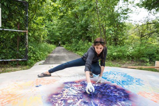 "Katherine Lampert of Chicago uses spray chalk and stencils to create her work on the sidewalk for the ""Trail Art - Site As Studio"" exhibition at the Trailside Museum of Natural History in River Forest. 