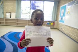 Youth in Y-Kids proudly displays his progress report from school.