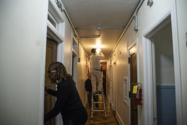 Maintenance worker installs a light in a hallway in the former convent. | Alexa Rogals/Staff Photographer