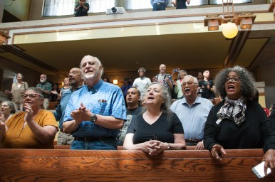 Those who attended Saturday's gathering at Unity Temple sing a song at the end of the event. | Shanel Romain