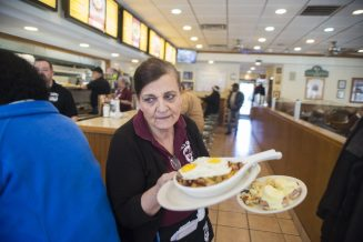 Server Roula Kourpas brings out plates of food to one of the tables during the lunch time rush at Al's Grill on Madison Street and Wisconsin Avenue in Oak Park.   ALEX ROGALS/Staff Photographer