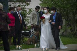 Eliot Smalheiser, right, walks Grace Guo down the sidewalk on Monday, May 18, 2020, during an outdoor wedding on Carpenter in Oak Park, Ill. | ALEX ROGALS/Staff Photographer