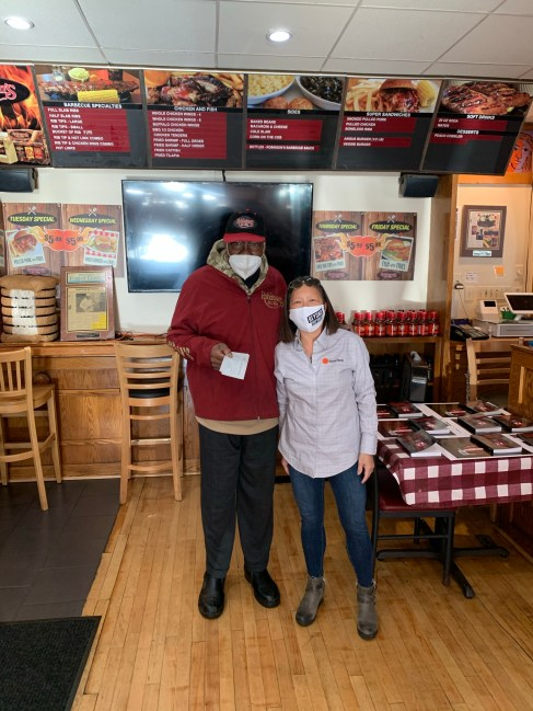 Byline Bank's Susie Goldschmidt bought 5,000 in gift cards from local restaurants including this purchase from Charlie Robinson at Robinson's #1 Ribs on Madison Street.