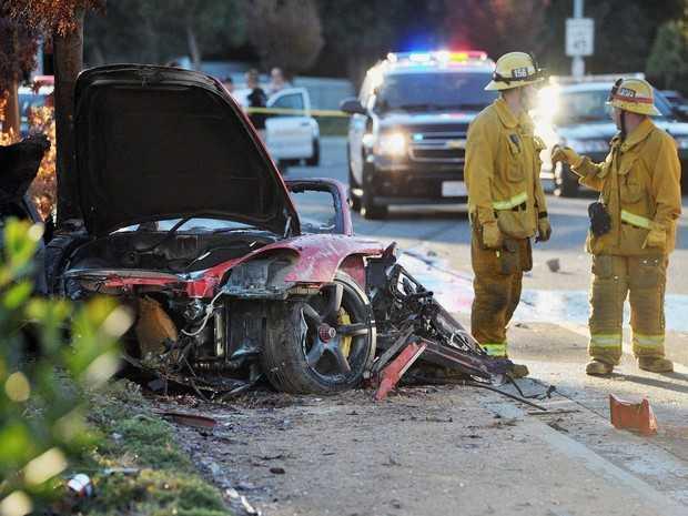 Bombeiros trabalham em Porsche destruído em acidente neste sábado em Valencia, na cidade de Santa Clarita, Califórnia. (Foto: AP Photo/The Santa Clarita Valley Signal, Dan Watson)