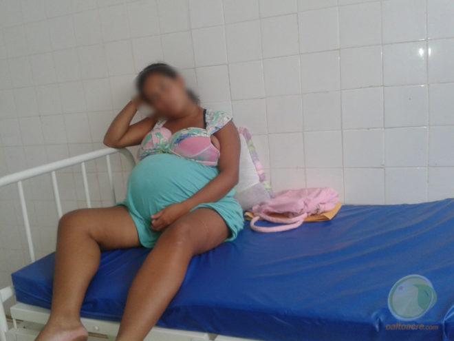 Paciente esperando para dar luz encima da cama sem lençol.