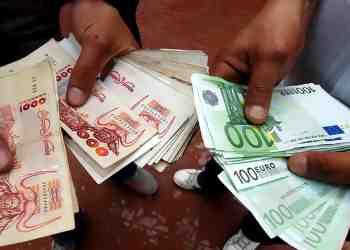 Deux individus s'échangeant des coupures de dinar et d'euro