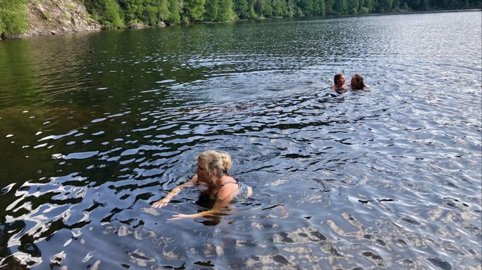 Trois personnes se baignent dans l'eau d'une rivière.