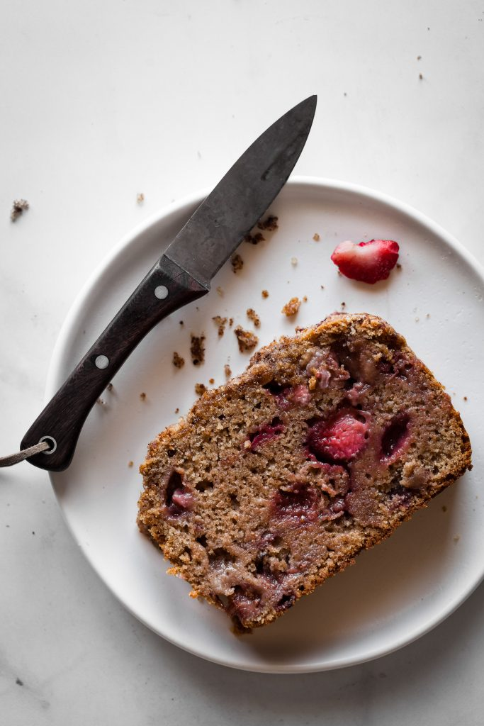 Slice of strawberry loaf on plate with knife.