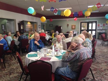Seniors socialize in the OCCOA dining room just before lunch.