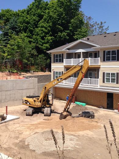 Marc Curtis of Hallack Contracting uses a long-stick excavator this afternoon to build and back-fill a retaining wall at Lake Pointe Apartments overlooking Hart Lake. Lake Pointe officials said the apartments will be ready for occupancy July 1.
