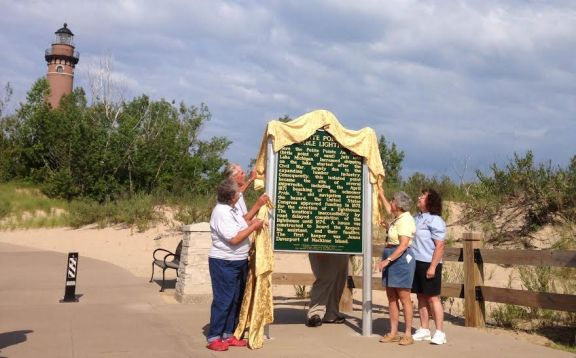 Original Lighthouse Seekers board members Mort Wiegand, Carl Wiegand, Yvonne Kessler and Claire Dennison unveil the historical marker at Little Sable Point Lighthouse. Mort is former president of the organization; Karl is current president; Claire is current secretary; and Yvonne is former treasurer.