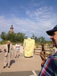 Steve Kantner (at right), who has admired the lighthouse for six decades at his summer residence in Silver Lake, holds a walking stick modeled after the lighthouse as Michigan Historical Commissioner Tom Truscott (at left) addresses the crowd. Peter Manting, executive director of Sable Point Lighthouse Keepers Association (SPLKA), stands next to the historical marker prior to the unveiling.