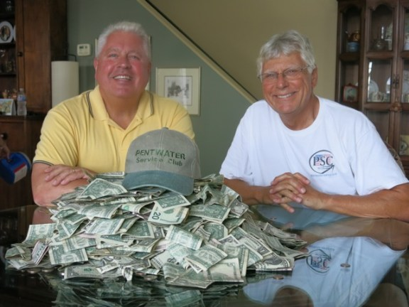 Pentwater Service Club members Kevin Dolle and Ron Beeber count the funds contributed by generous Homecoming Parade spectators -- almost $3,000.