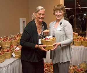 Top honoree Judy Thiel accepts her gift basket from hospital staff member Bonnie VanderZanden of Oceana County, who spent a good many hours washing apples and assembling gifts for the 126 hospital volunteers. The baskets also contained ingredients for making apple crisp.