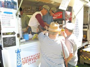 """Mike Flynn and Don Sproul serve customers from the Club's iconic """"Bill Duncan Food Wagon"""" on Pentwater's Village Green. Proceeds are donated to worthy local causes."""